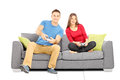 Young couple sitting on a modern couch and playing video games isolated white background Stock Photos