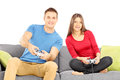 Young couple sitting on a modern sofa and playing video game isolated white background Stock Photo