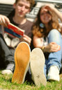 Young couple sitting near auto closeup feet image sneakers of the car Royalty Free Stock Image