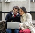 Young couple sitting outside on bench looking at laptop screen portrait of a Royalty Free Stock Photo