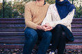 Young couple sitting on park bench a youg is and holding each other a in autumn Stock Photos