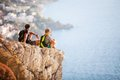 Young couple sitting on rock and enjoying view beautiful Royalty Free Stock Photography