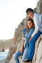 Young couple sitting on rocks at seaside. Royalty Free Stock Photo