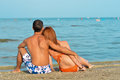 Young couple sitting on sandy beach and embracing happy summer outdoors background Royalty Free Stock Photos