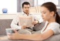 Young couple sitting separated in living room men reading newspaper women drinking tea bored Royalty Free Stock Photo