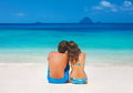 Young couple sitting together on the beach happy loving close and looking to a clear horizon Stock Photo