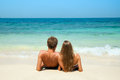 Young couple sitting together sand sea looking to horizon Royalty Free Stock Photos