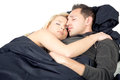Young couple sleeping in bed entwined each others arms as they enjoy happy dreams and a restful sleep Stock Images