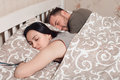 Young couple sleeping in bed under blanket. Royalty Free Stock Photo