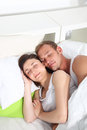 Young couple sleeping peacefully in bed lying close together with happy smiles as they enjoy their dreams Royalty Free Stock Image