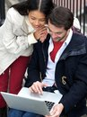 Young couple smiling and looking at laptop outdoors portrait of a Royalty Free Stock Image