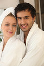 Young couple smiling wearing bathrobe portrait of all smiles Stock Image