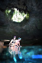 Young couple snorkel devils den a sit on the swim platform steps preparing to enter and in the clear freshwater springs grotto at Royalty Free Stock Image