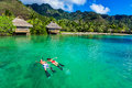 Young couple snorkeling over reef next to resort on a tropical i island with water villas Royalty Free Stock Photo