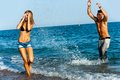 Young  couple splashing water at sea side. Royalty Free Stock Photos