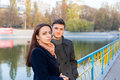 Young couple standing on bridge in urban park waist up portrait of fashionable together over small lake sunny autumn day Royalty Free Stock Photo