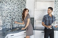 Young couple standing in model home kitchen while looking at each other Stock Photos