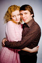 Young couple standing together posing in studio looking at ca camera red haired curly woman Stock Images