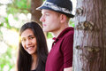 Young couple standing among trees sunlight streaming interracial Royalty Free Stock Photos