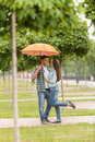 Young couple standing under umbrella in park blurred view of tree with focus on men huging woman Royalty Free Stock Photo