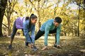 Young couple stretching before running in city park. On the move Royalty Free Stock Photo