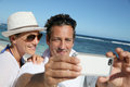 Young couple on summer holidays taking photo at the beach making a selfy with smartphone Royalty Free Stock Image