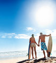 Young couple with surf boards at the sea shore Royalty Free Stock Photos