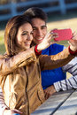 Young couple taking photos with smartphones in the park portrait of photo Royalty Free Stock Photography