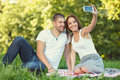 Young couple taking a self portrait in the park meadow Stock Photography