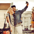 Young couple taking self portrait photo at old camera outdoors Stock Photo