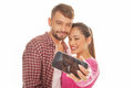Young couple taking a self portrait smiling as they pose close together looking into the camera on their smartphone isolated on Stock Photography