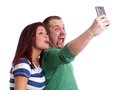 Young couple taking selfie making silly faces while a self portrait with smart phone Royalty Free Stock Image