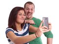Young couple taking selfie making silly faces while a self portrait with smart phone Royalty Free Stock Photography