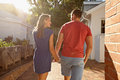 Young couple taking a walk in their backyard rear view shot of holding hand hand outside loving outdoors on Royalty Free Stock Photography