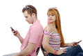 Young couple talking on mobile phones sitting back to back. Royalty Free Stock Photo