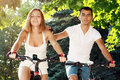 Young couple on their bikes fitness healthy beautiful soft summer colors focuse men face Royalty Free Stock Image