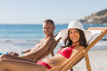 Young couple on their deck chairs smiling at camera while sunbathing the beach Royalty Free Stock Photography