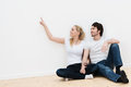 Young couple in their new home sitting on the bare wooden floor an empty room Royalty Free Stock Images