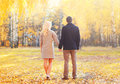 Young couple together holding hands walking in warm sunny autumn day view back