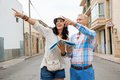 Young couple of tourists consulting a map trendy attractive as they search for their destination while out sightseeing on their Stock Photos