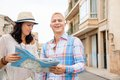 Young couple of tourists consulting a map trendy attractive as they search for their destination while out sightseeing on their Stock Images
