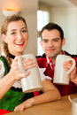 Young couple in traditional Bavarian Tracht in restaurant or pub Royalty Free Stock Image