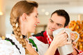 Young couple traditional bavarian tracht restaurant pub pretzel beer Stock Photo
