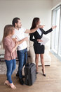 Young couple with travel case meeting with broker, apartment vie Royalty Free Stock Photo