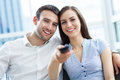 Young couple with tv remote smiling Royalty Free Stock Photo