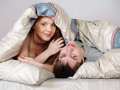 Young couple under a blanket in a bed Royalty Free Stock Photos