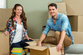 Young couple unpacking carton boxes in their new house assisting each other while Royalty Free Stock Image