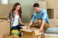 Young couple unpacking carton boxes in their new house assisting each other while Royalty Free Stock Photography