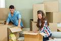 Young couple unpacking carton boxes in their new house assisting each other while Stock Photography