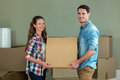 Young couple unpacking carton boxes in their new house posing while Royalty Free Stock Photography